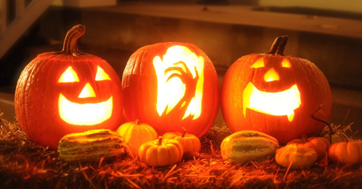 three carved and lit up Halloween pumpkins