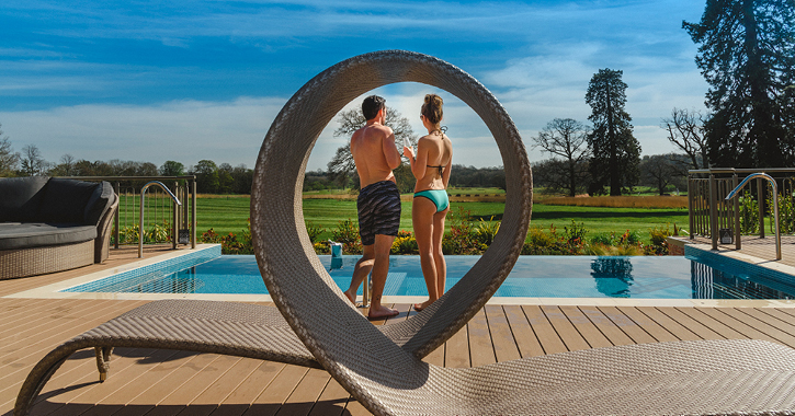 couple standing outside with drinks at Rockliffe Hall Hotel Spa on a sunny day