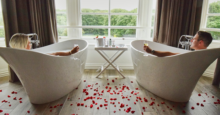 couple in matching bath tubs with rose petals on the ground in a hotel room at Seahm Hall.