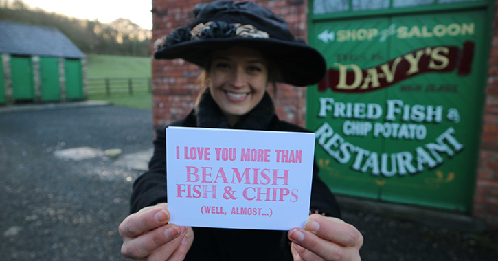 Woman dressed in 1900s costume at Beamish Museum holding a Valentine's postcard