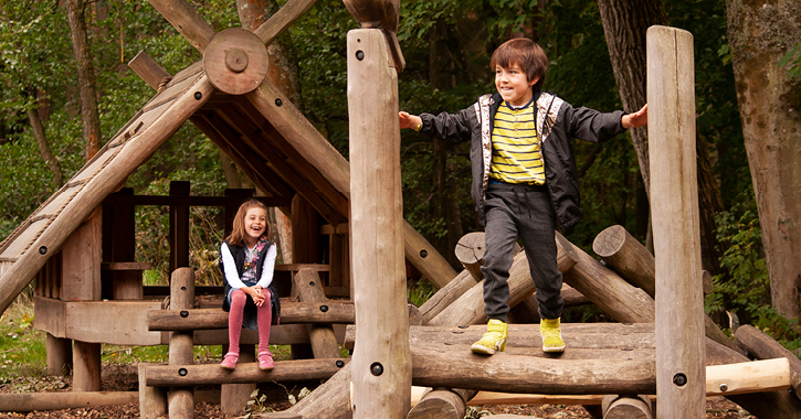 boy and girl playing on woodland play area