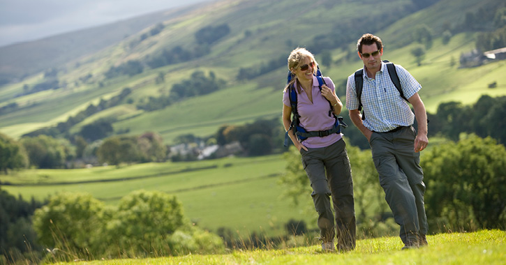 couple walking through the Durham dales landscape on a sunny day.