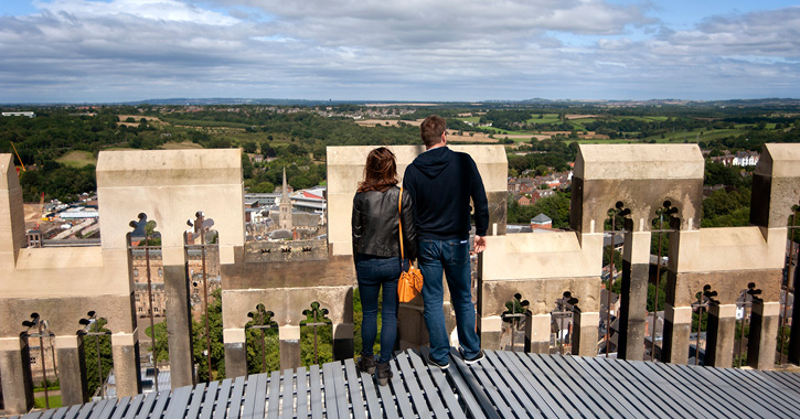 Couple looking over edge on the top of Durham Cathedral central tower