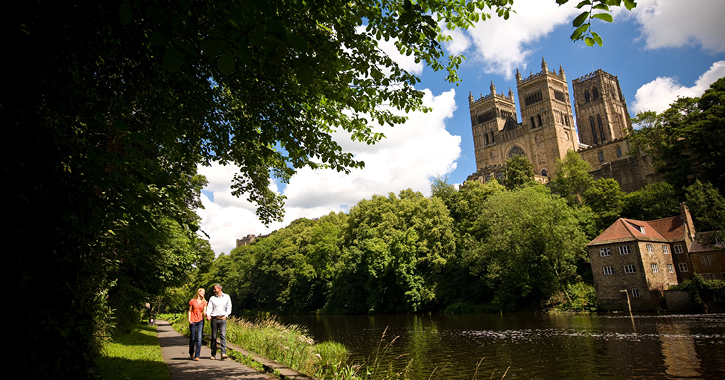 couple walking along river bank at Durham City
