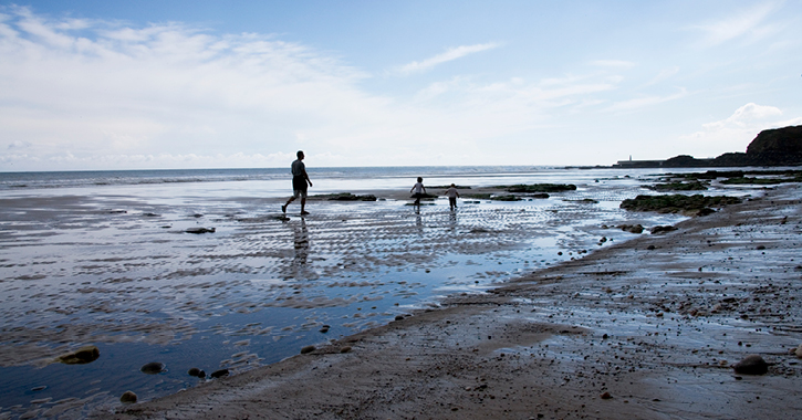 Father walking with two children on Seaham Beach, County Durham