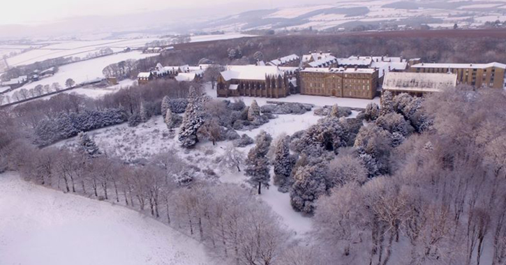 aerial shot of Ushaw historic house, chapels and garden covered in snow