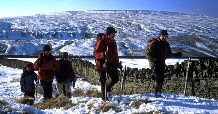 group of people walking through the north pennines in snow during winter