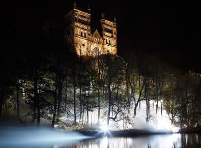 Durham Cathedral lit up at night with Fogscape art installation in the foreground