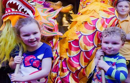 Three children celebrating Chinese New Year, holding a Chinese Dragon