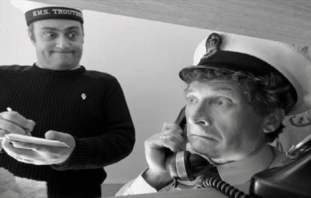 black and white image of two sailors, one on the telephone the other with notepad and pen taking notes
