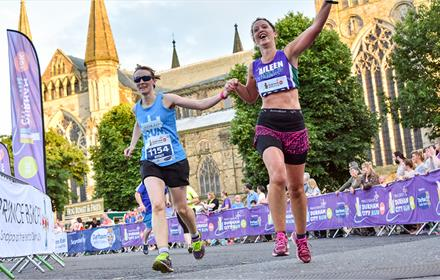 Female runners crossing the finish line of the Durham City Run