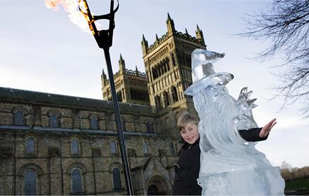 child enjoying ice sculpture at fire and ice festival in Durham.